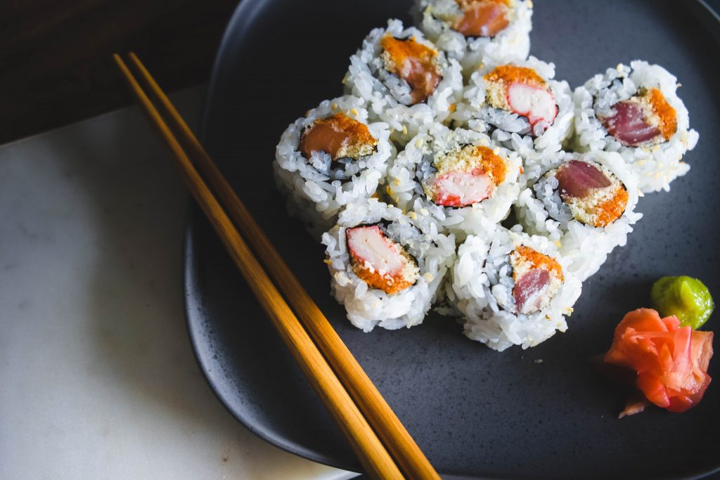 sushis avec baguettes dans une assiette foncée