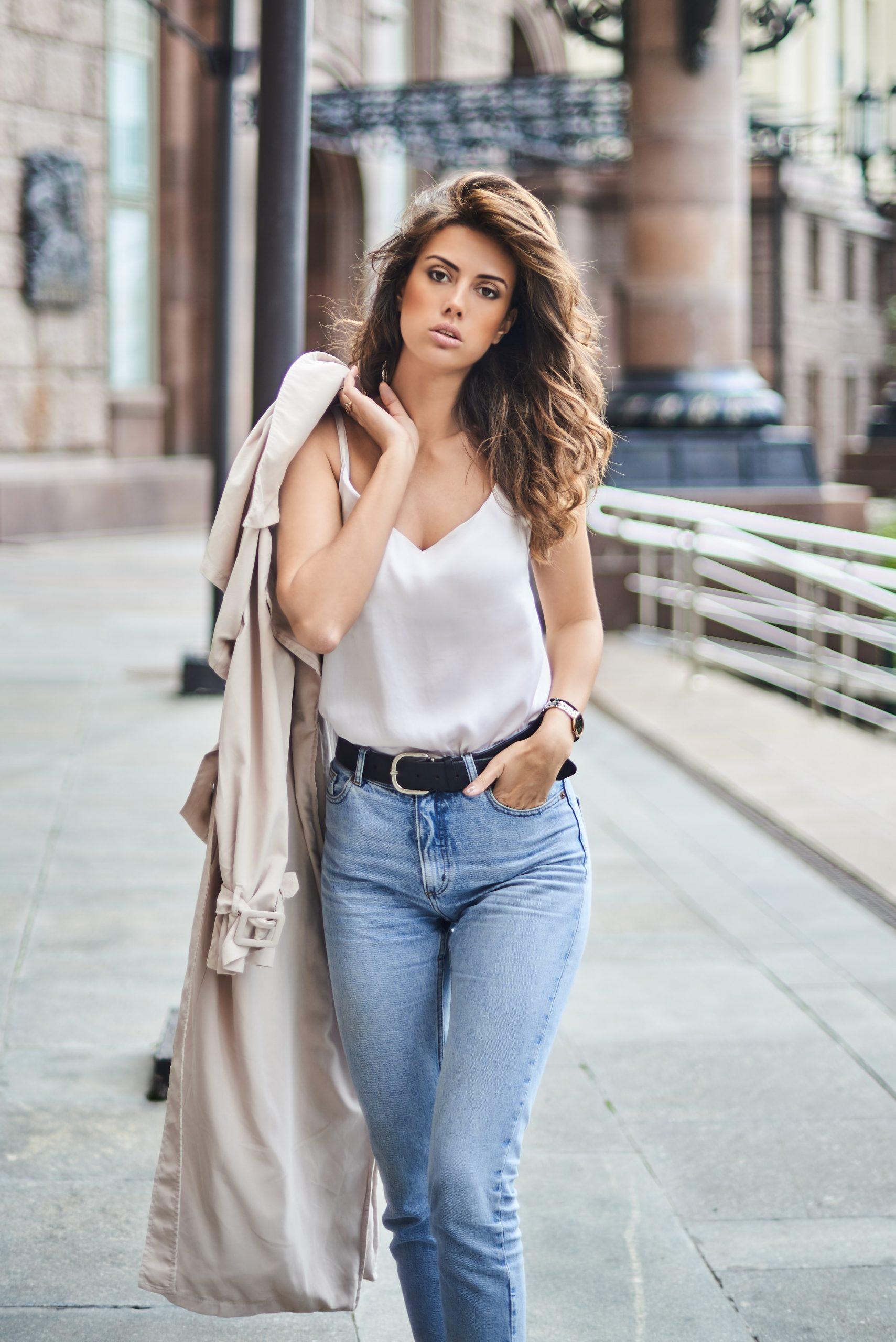 femme portant un débardeur blanc un jean et un trench sur l'épaule