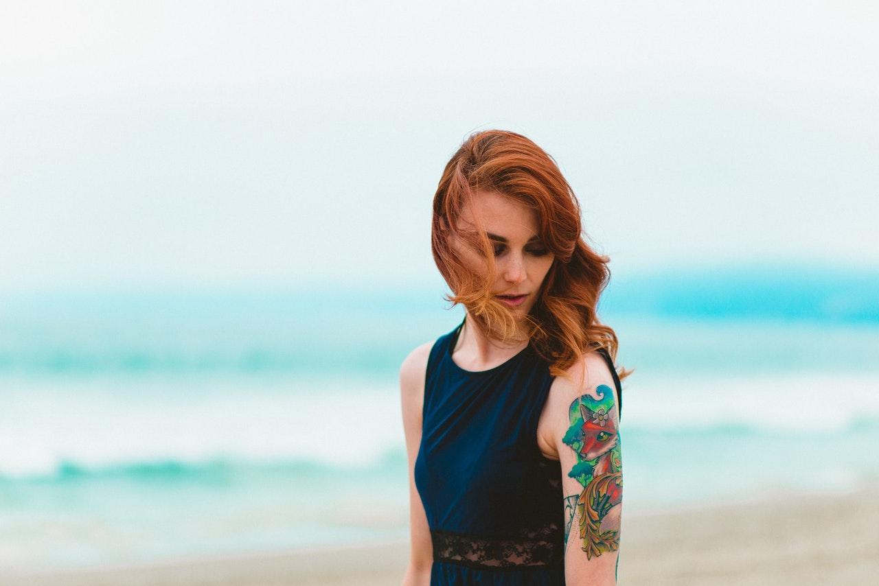 jeune femme sur une plage avec un tatouage coloré sur le bras