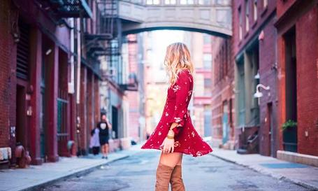 femme blonde portant une robe rouge courte et des cuissardes camel