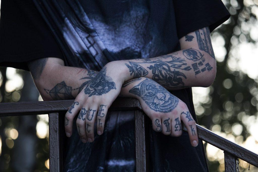 personne avec des tatouages sur les mains et les avant-bras