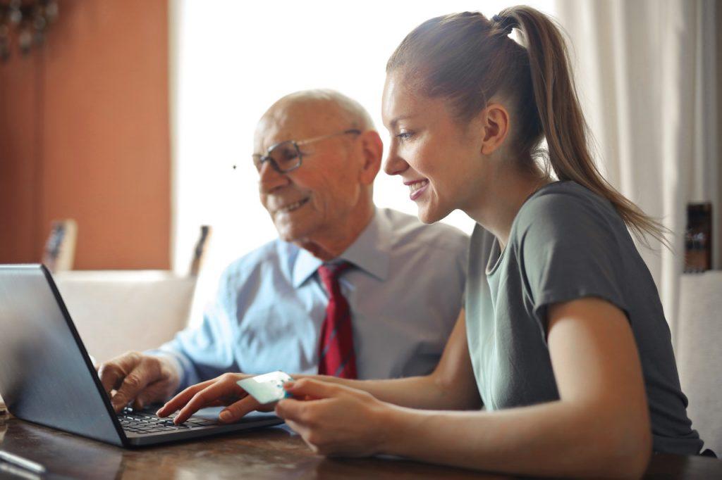 jeune femme qui aide un senior à utiliser l'ordinateur