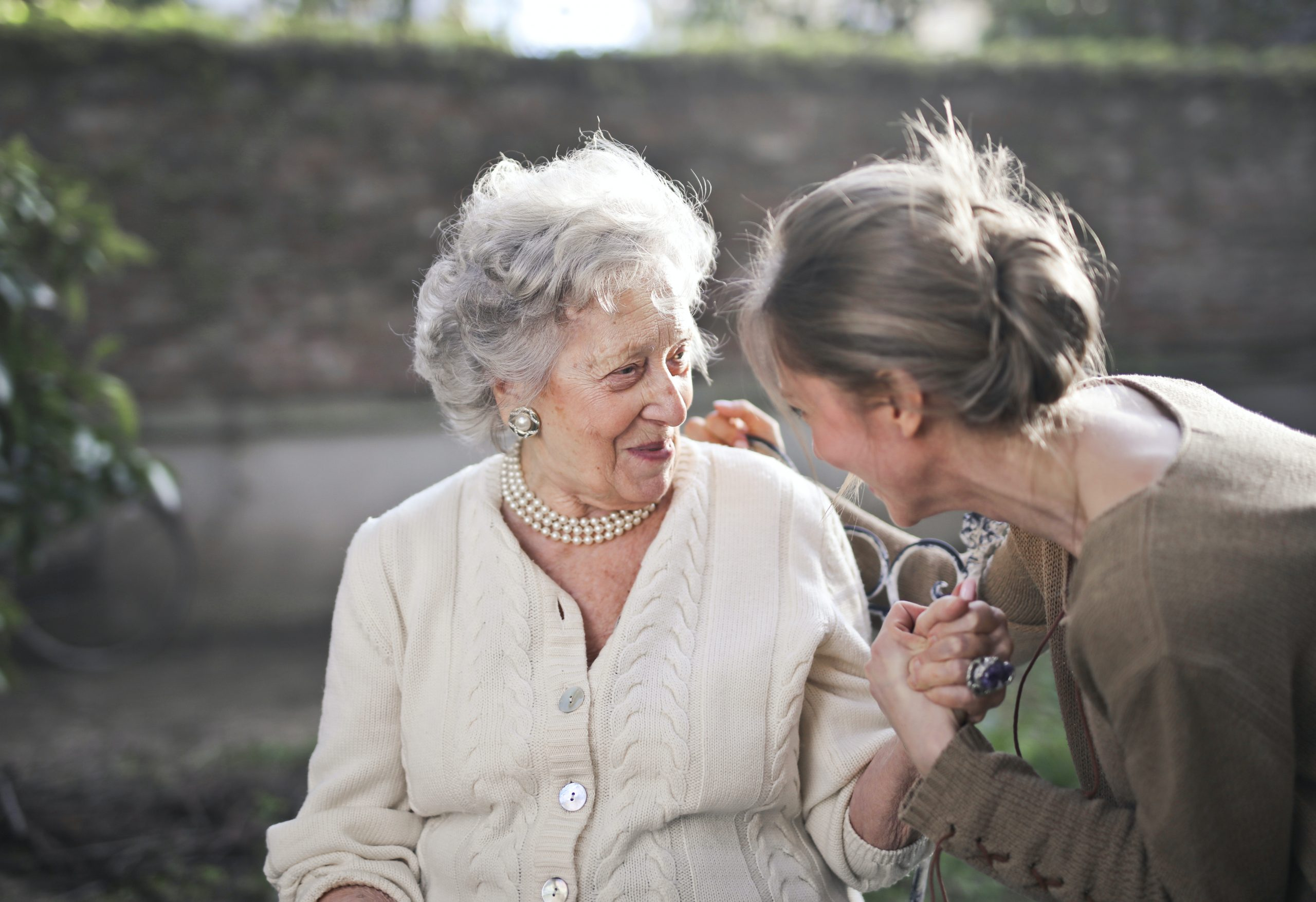 personne âgée qui tient la main de son aide à domicile