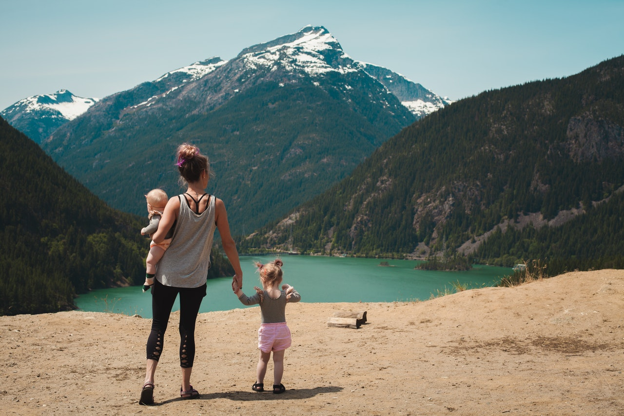 maman qui porte son bébé et qui tient la main à sa petite fille