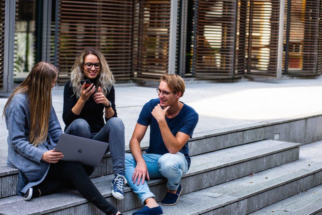 trois jeunes assis sur des marches